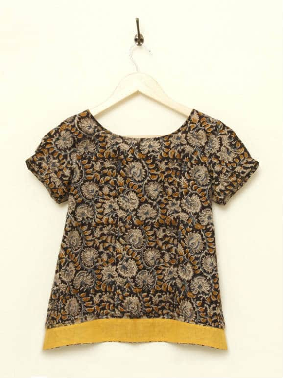 Cotton Kalamkari Tunic with an asymmetrical hemline and folded sleeve edge. The back length extends beyond the length of the front, with a thin contrasting band of yellow on the reverse side. Hand printed with organic dyes